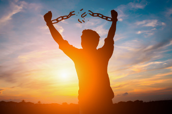 Man breaking the chains around his arms at sunset.